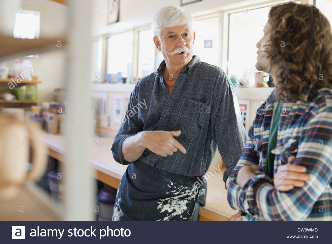 Pottery members talking in studio - Stock Image