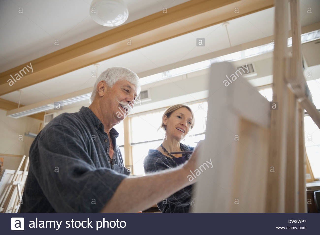Instructor and student looking at painting on easel - Stock Image