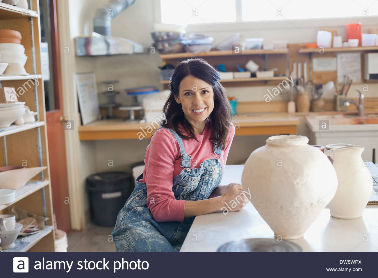 Portrait of confident female potter in glazing studio - Stock Image