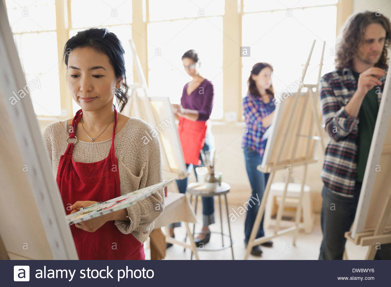 Female student painting in art class - Stock Image