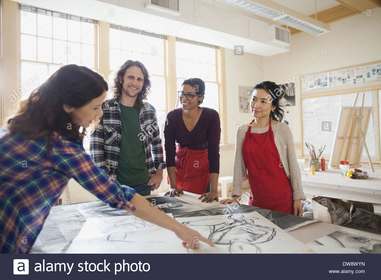 Students analyzing charcoal drawings in art studio - Stock Image