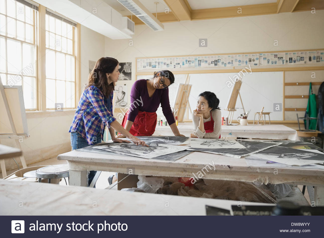 Students analyzing charcoal drawings in art class - Stock Image