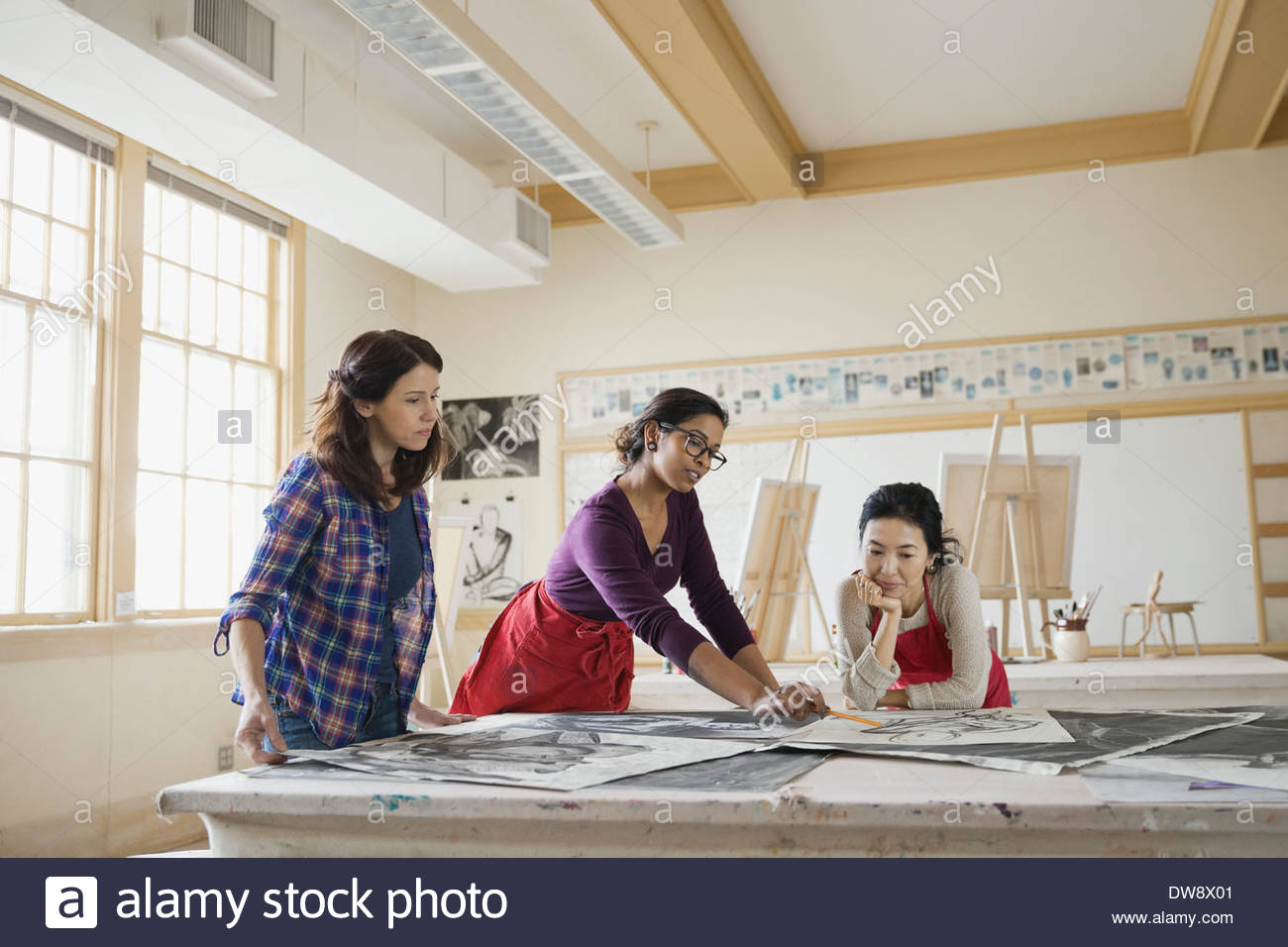 Students examining charcoal drawings in art class - Stock Image