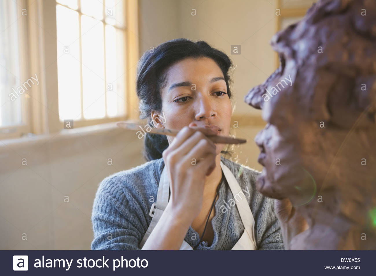 Artist working on clay sculpture in pottery studio - Stock Image