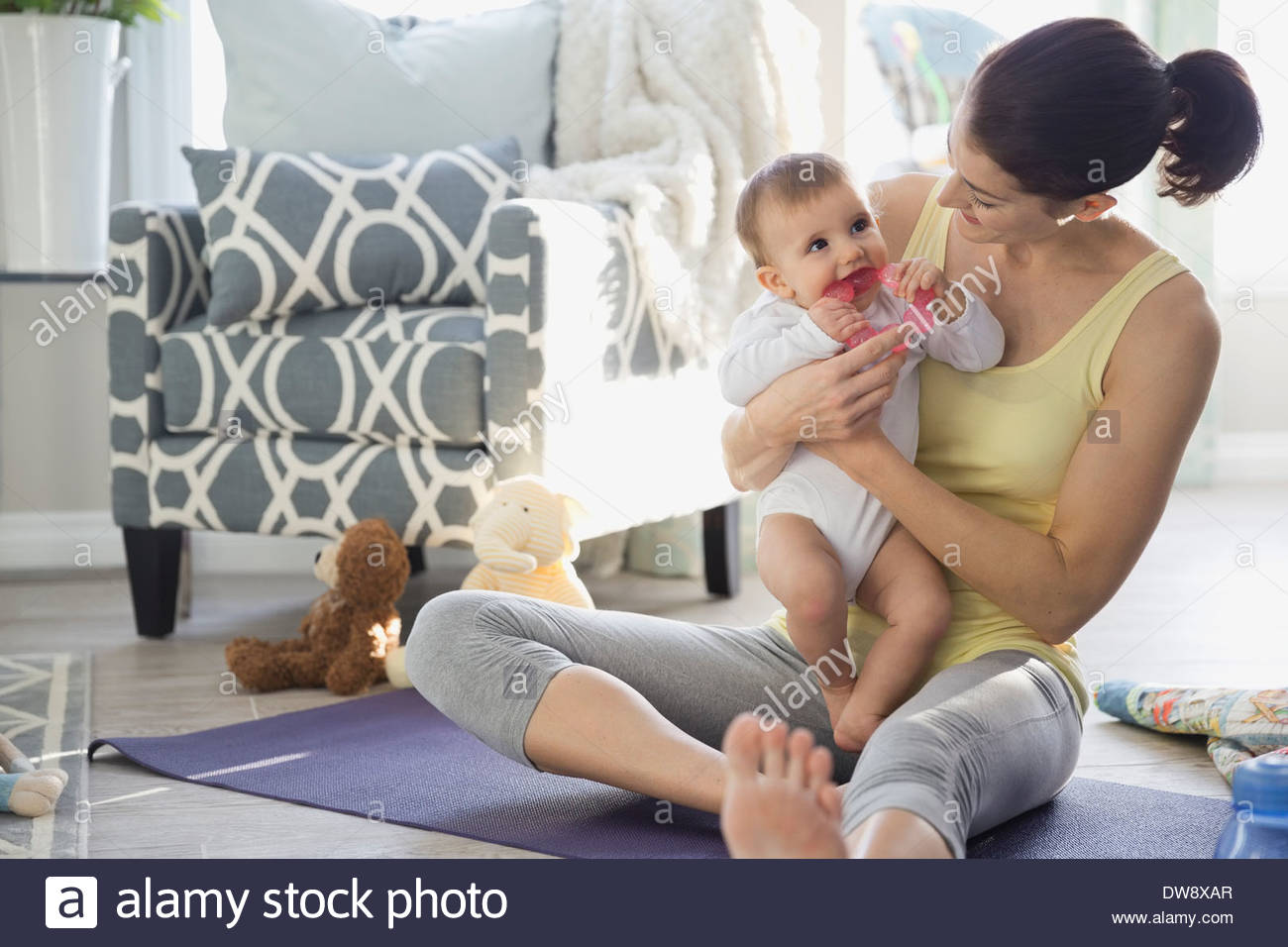 Mother sitting with baby on yoga mat at home - Stock Image