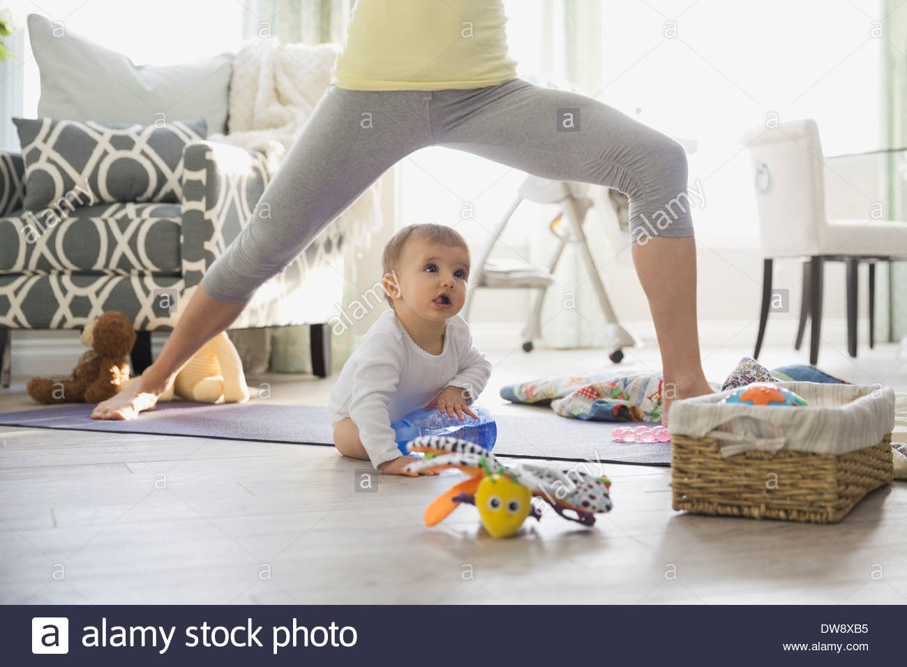 Mother practicing yoga by baby at home - Stock Image
