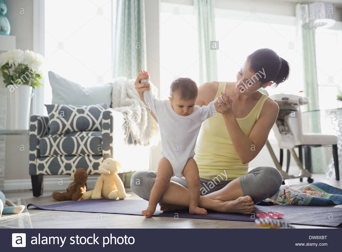 Mother playing with baby girl on exercise mat at home - Stock Image
