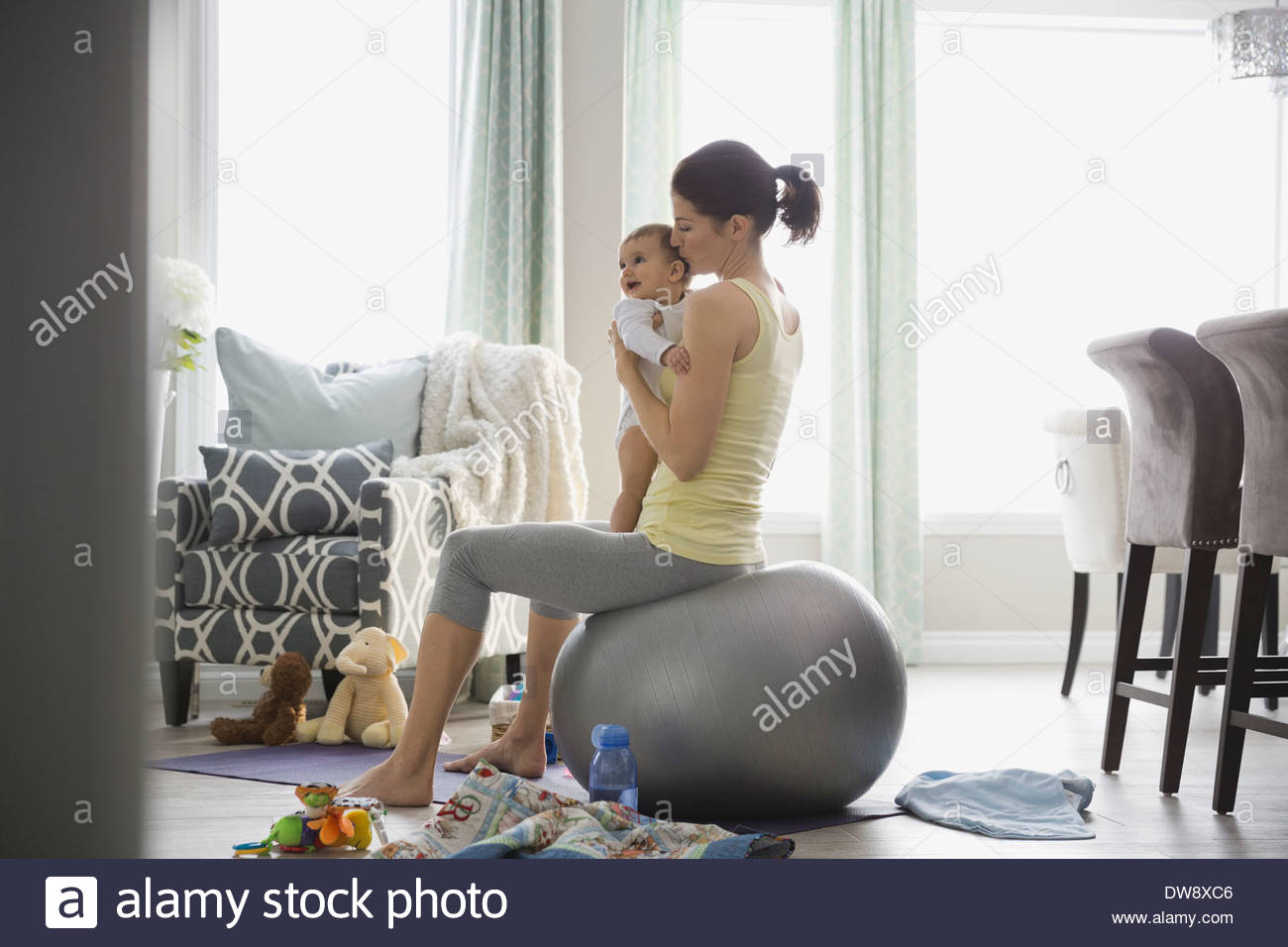 Mother with baby girl balancing on exercise ball - Stock Image
