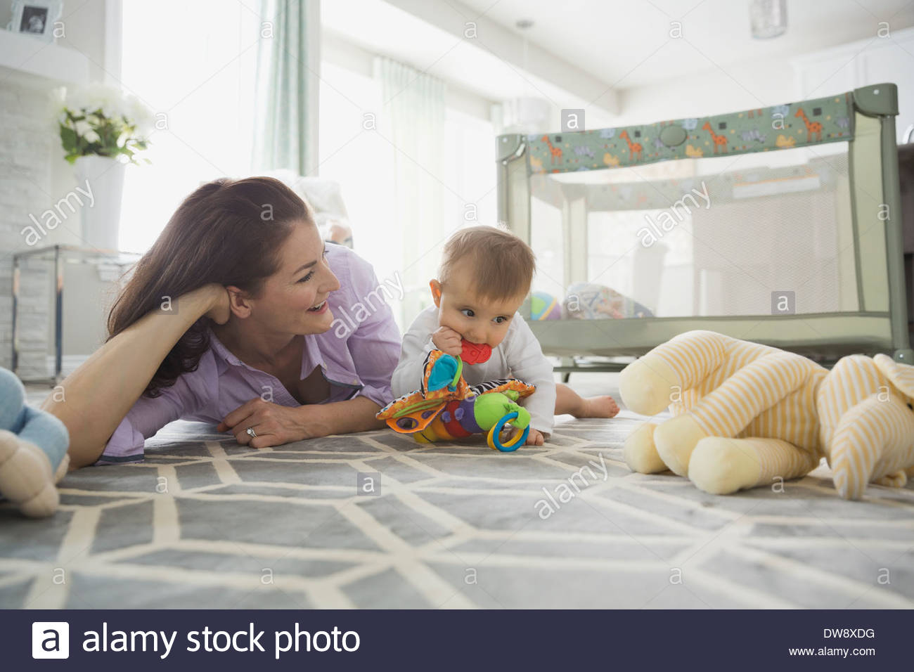 Mother and baby girl playing with toys on floor Stock Photo