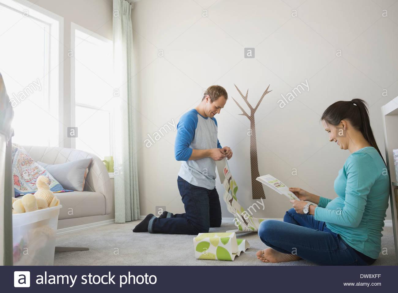 Expectant couple decorating nursery - Stock Image