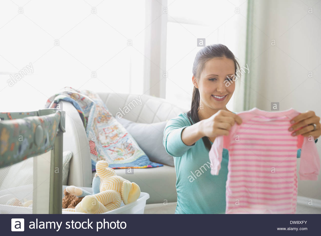 6203b0896 Pregnant woman holding baby onesie in nursery - Stock Image