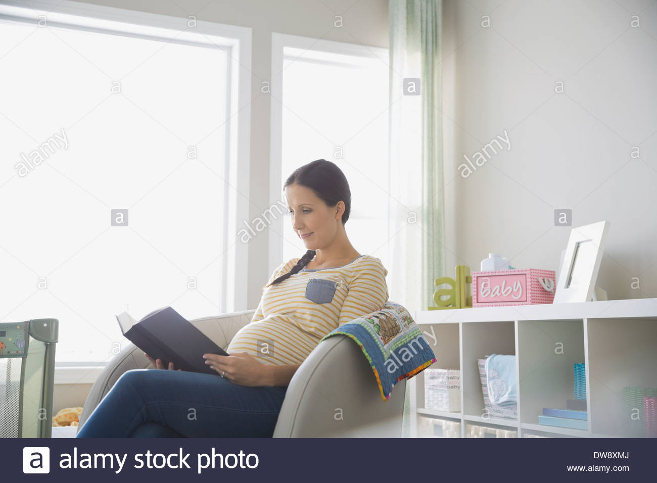 Pregnant woman reading book at home - Stock Image