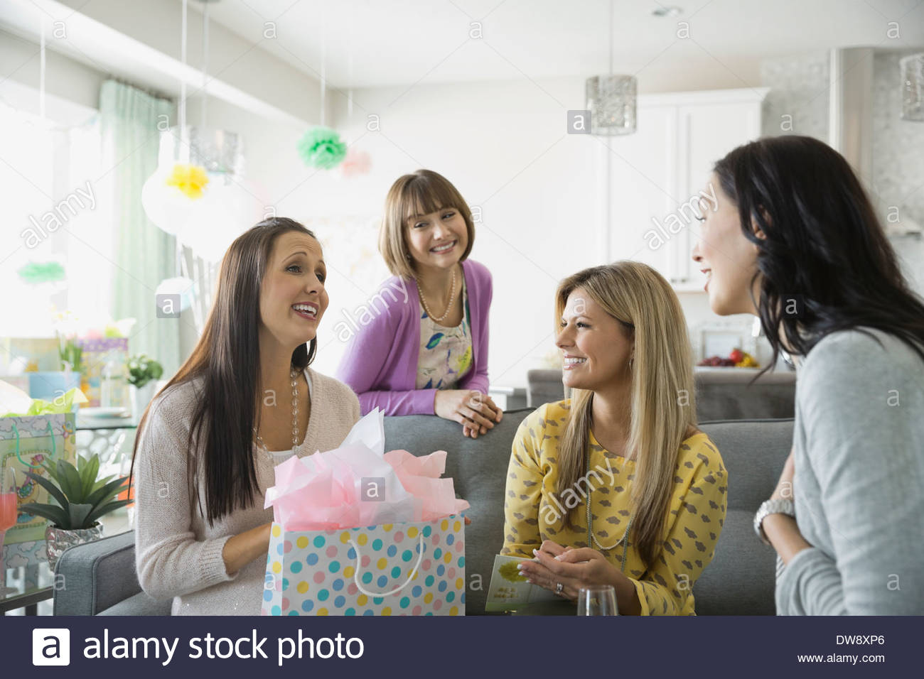 Woman opening gift at baby shower - Stock Image