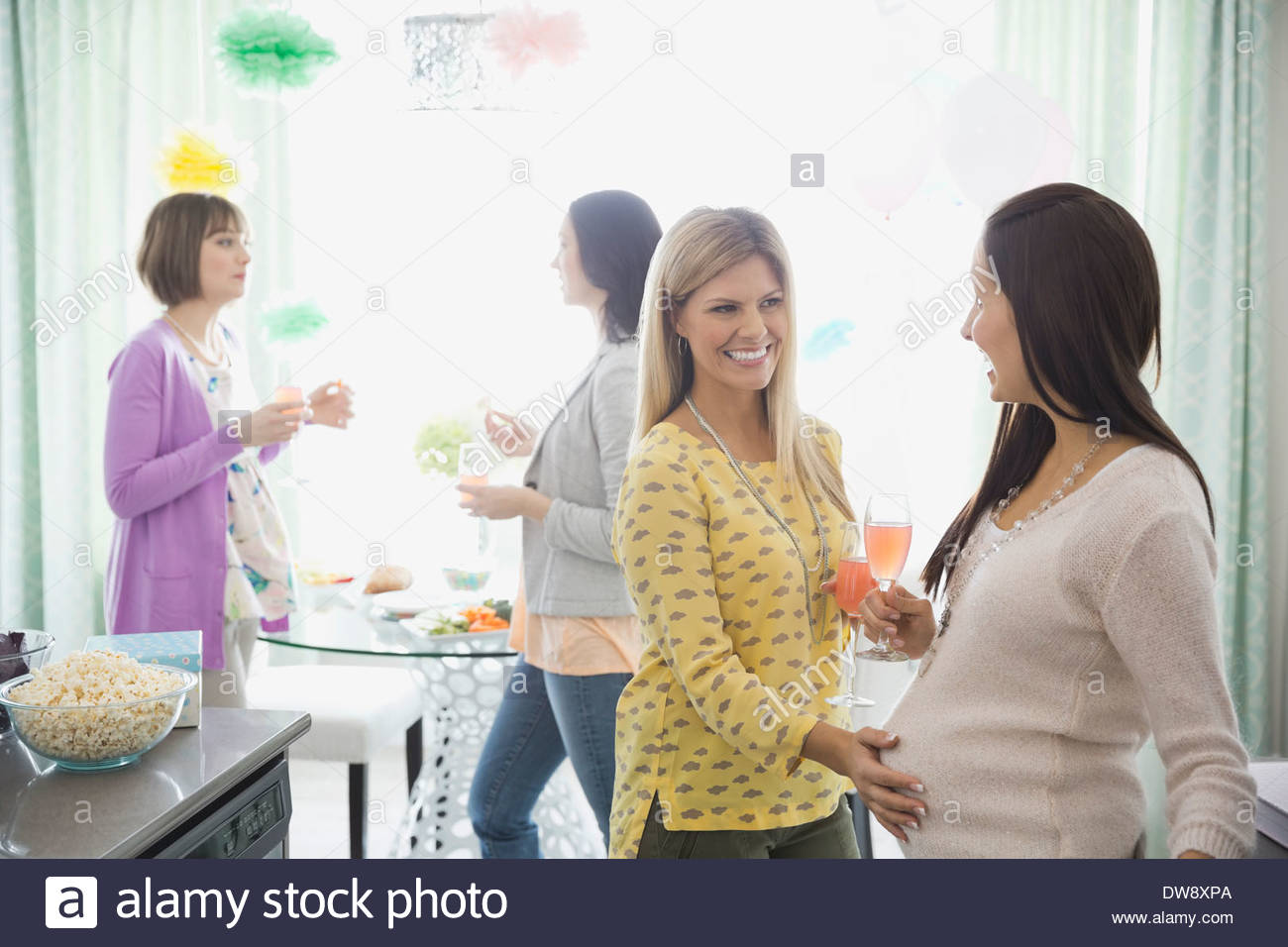 Friend touching pregnant womans belly at baby shower - Stock Image