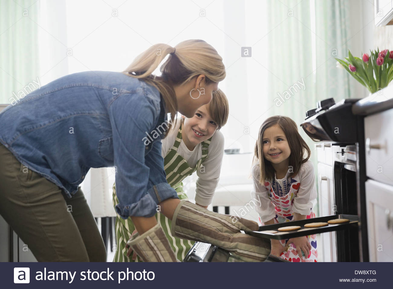 Mother and children baking cookies in kitchen - Stock Image