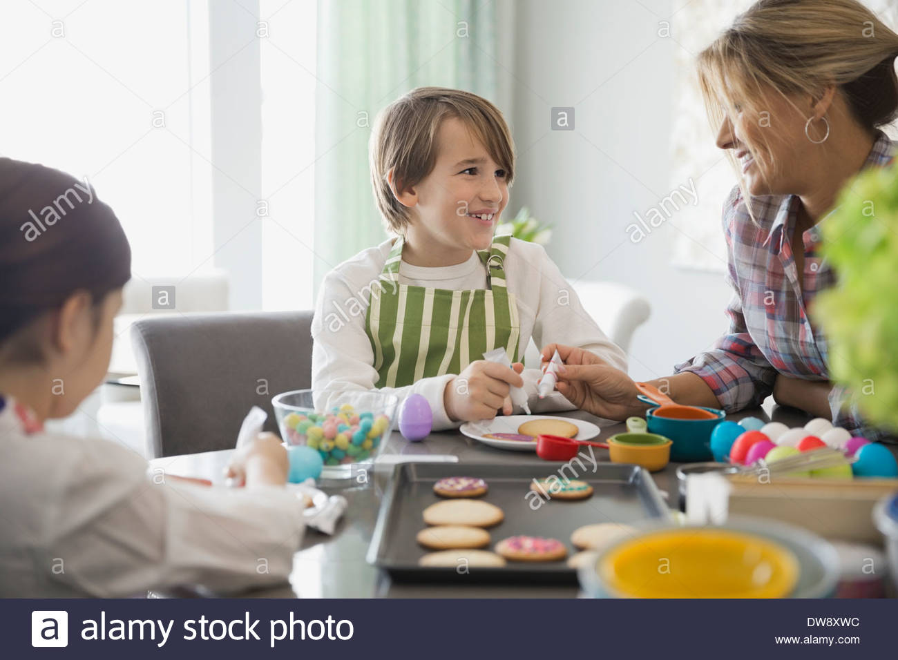 Mother and son decorating cookies at table - Stock Image