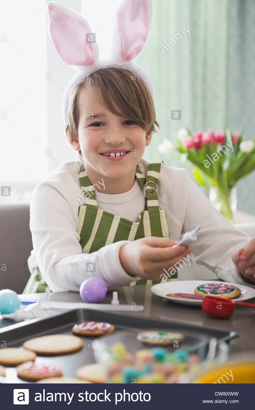 Portrait of boy wearing rabbit ears decorating Easter cookies - Stock Image