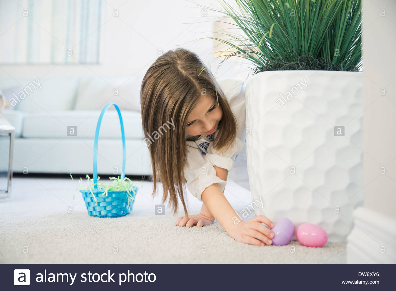 Girl collecting Easter eggs at home - Stock Image