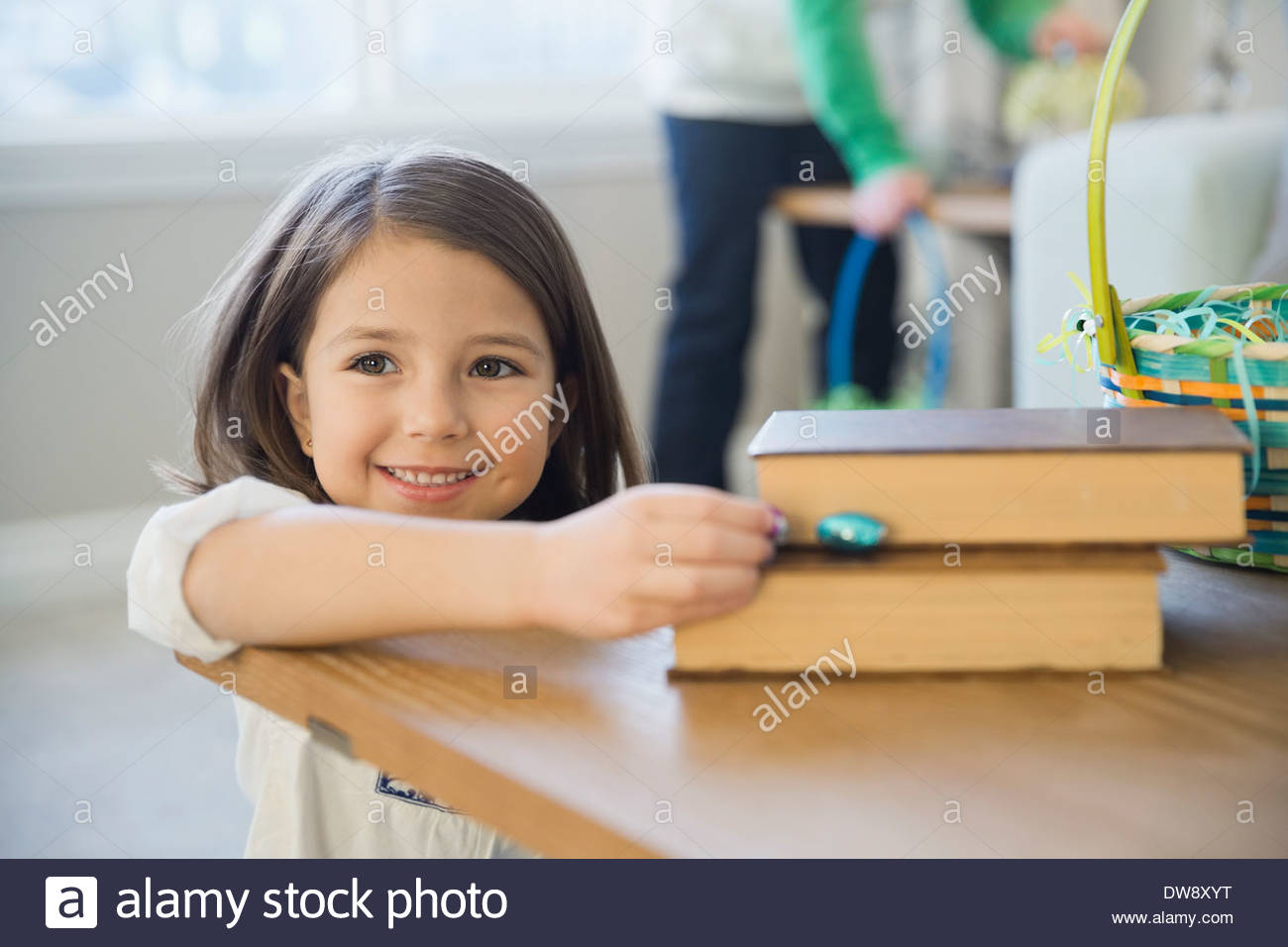 Cute girl collecting chocolate Easter eggs at home - Stock Image