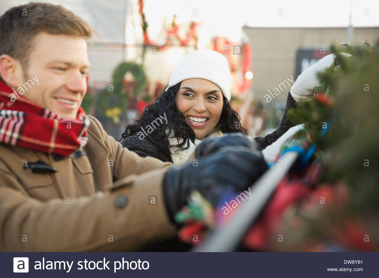 Portrait of couple tying down Christmas tree to car roof - Stock Image