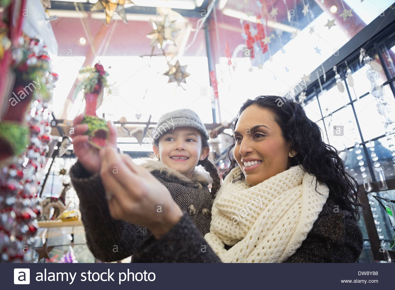 Mother and daughter buying Christmas ornaments in store - Stock Image