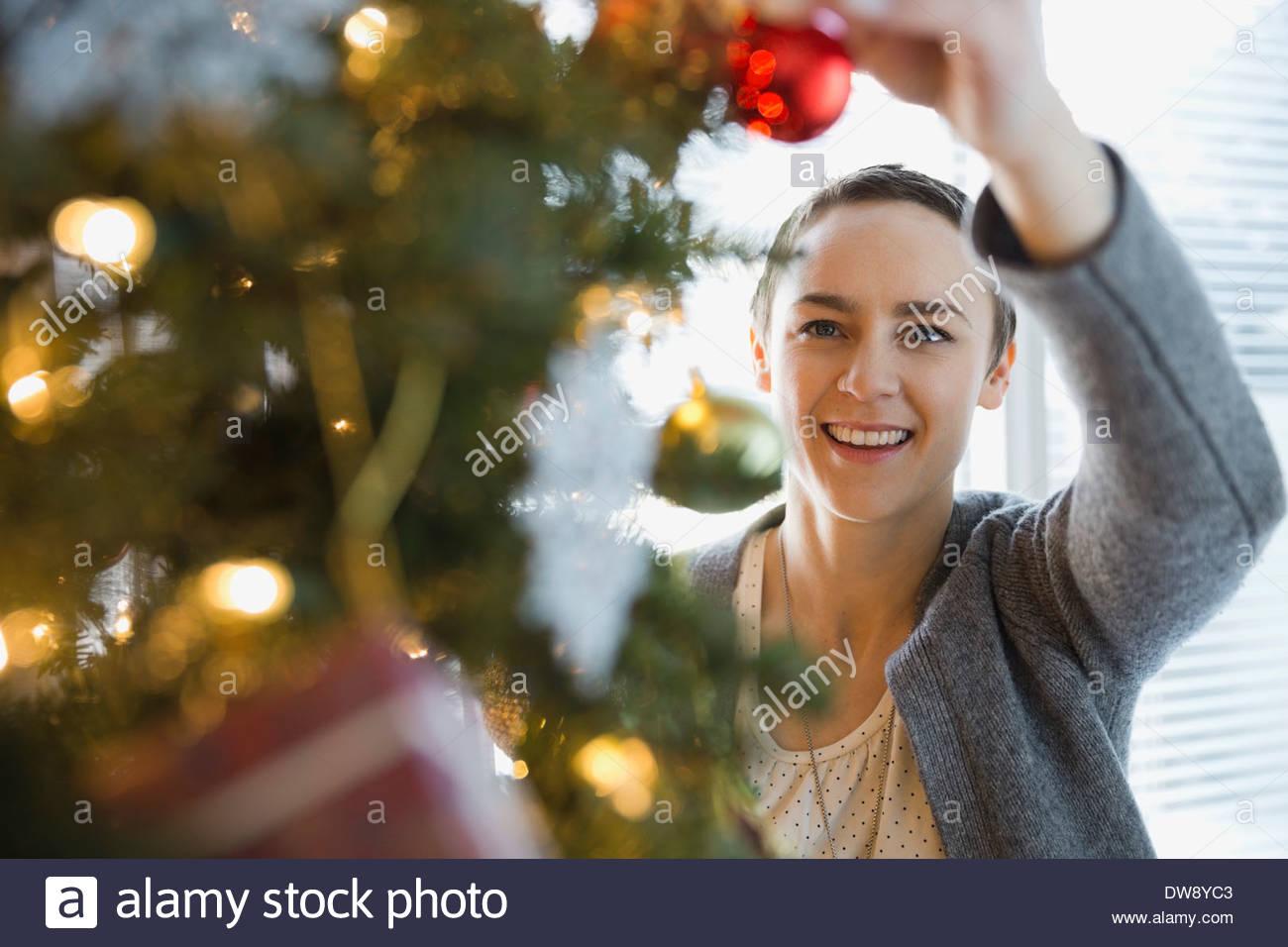 Woman decorating Christmas tree at home - Stock Image
