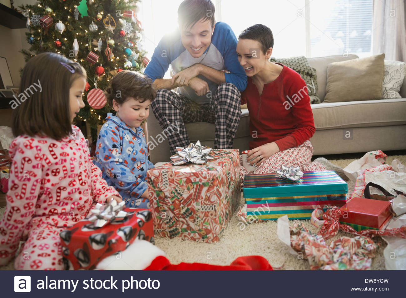 Family sitting with Christmas gifts in living room - Stock Image