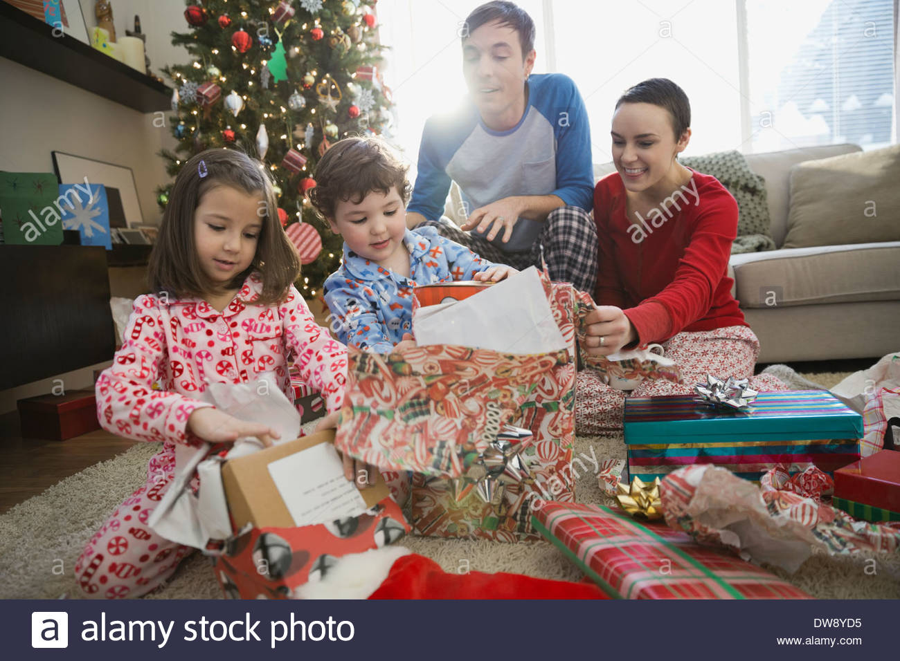 Christmas Gifts For Parents.Parents Watching Children Opening Christmas Gifts Stock