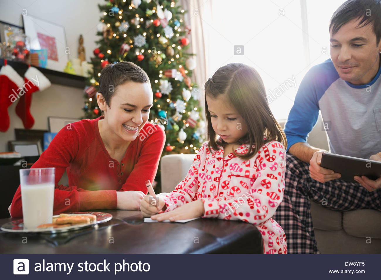 Parents helping girl write letter to Santa Claus - Stock Image