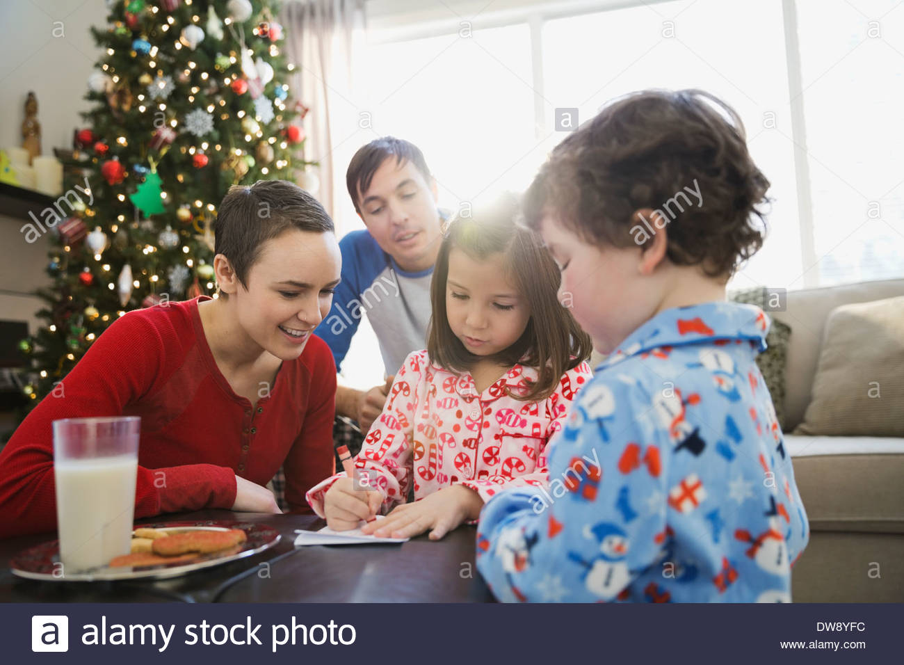 Family watching girl write letter to Santa Claus - Stock Image