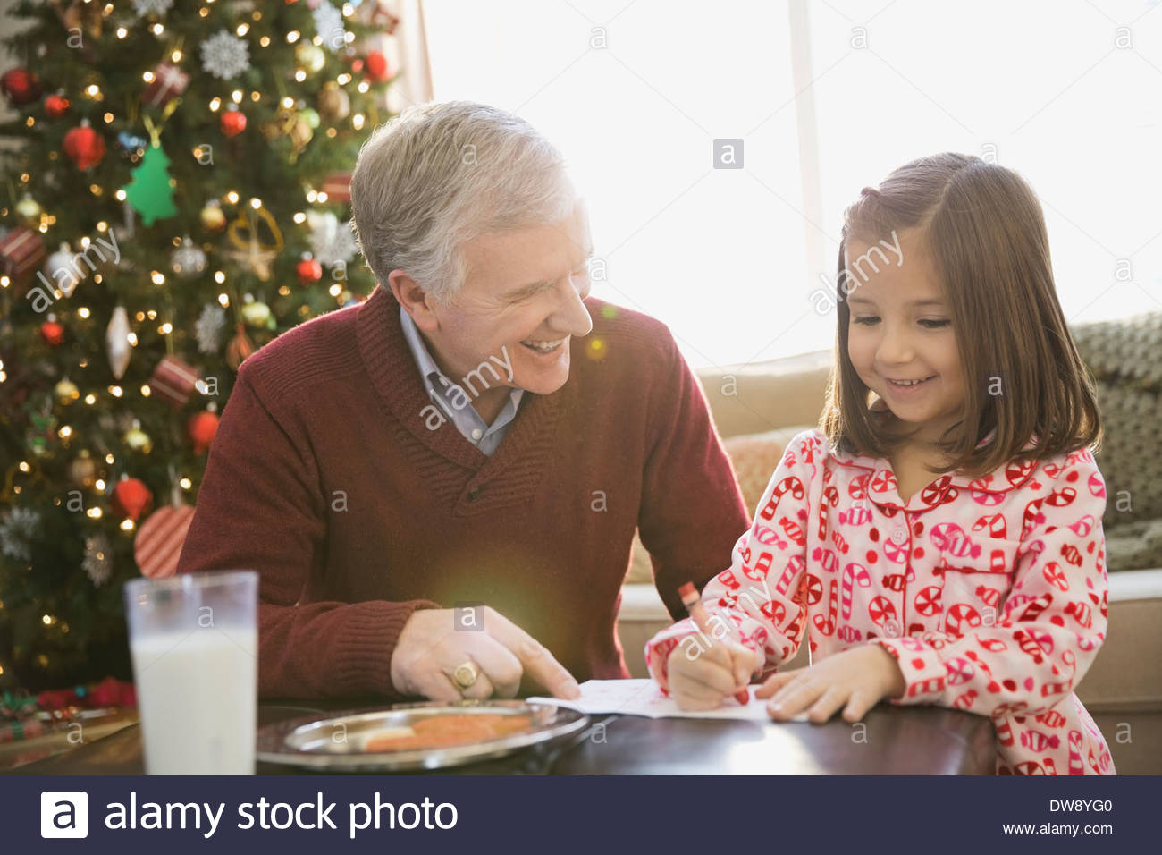 Grandfather helping girl write letter to Santa Claus - Stock Image