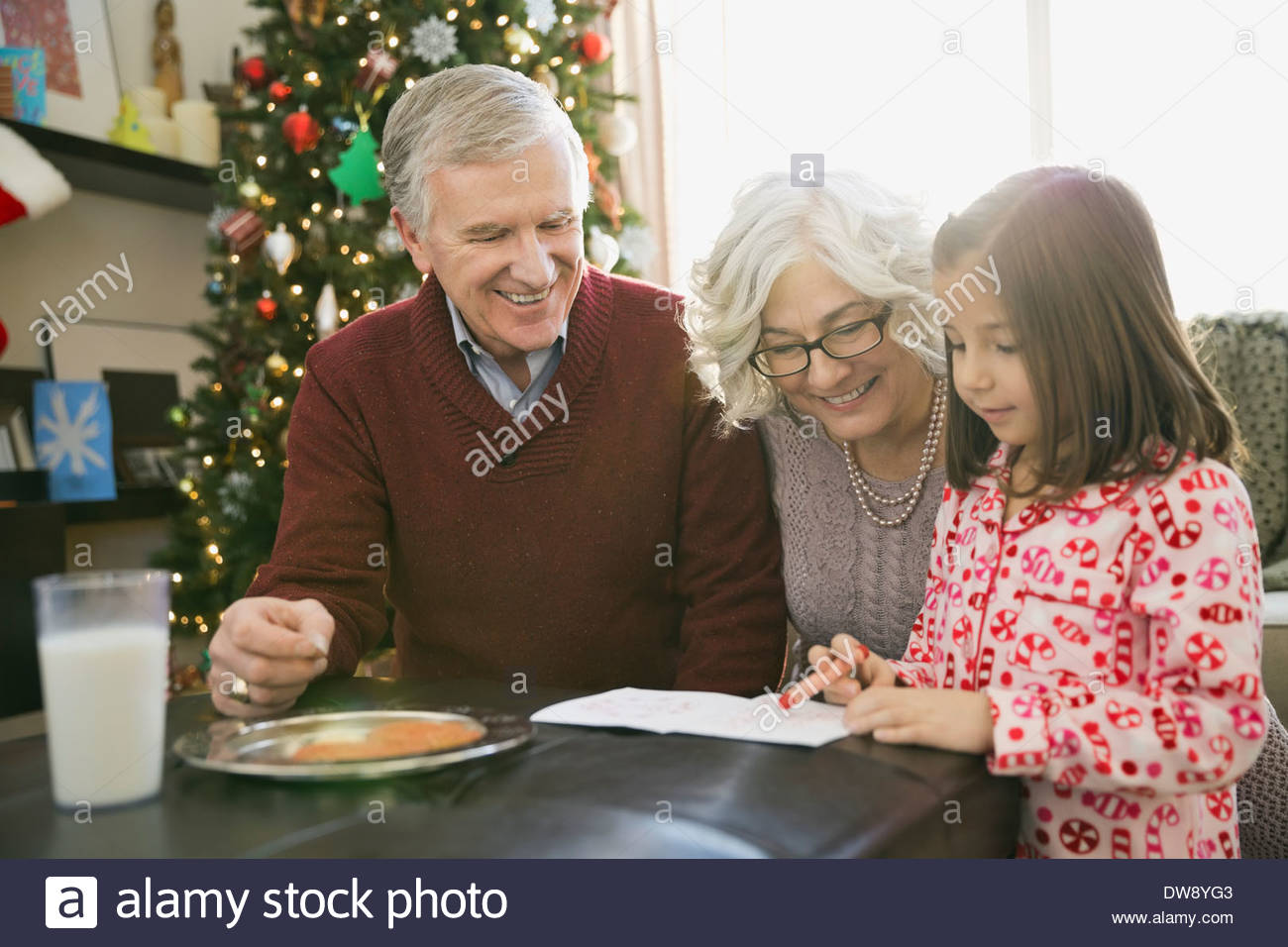 Grandparents helping girl write letter to Santa Claus - Stock Image