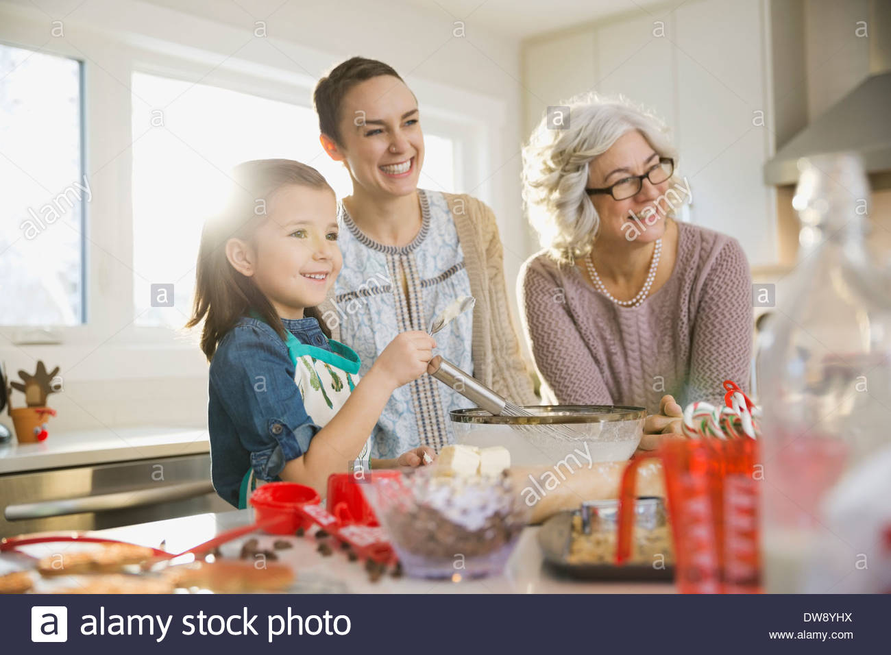 Three generation family baking cookies at Christmas - Stock Image