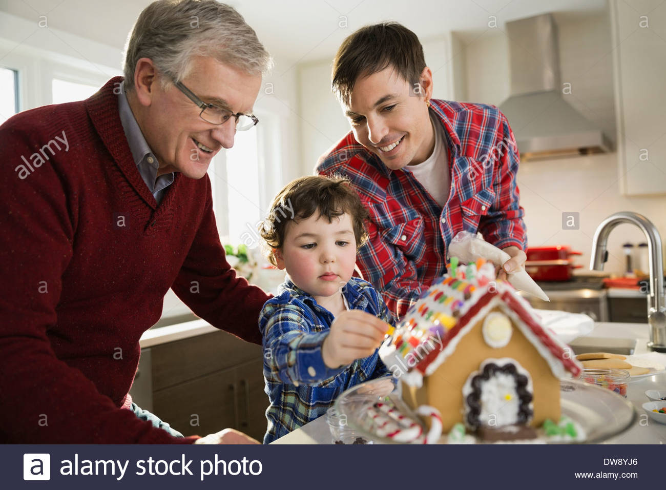 Three generation family decorating gingerbread house together - Stock Image