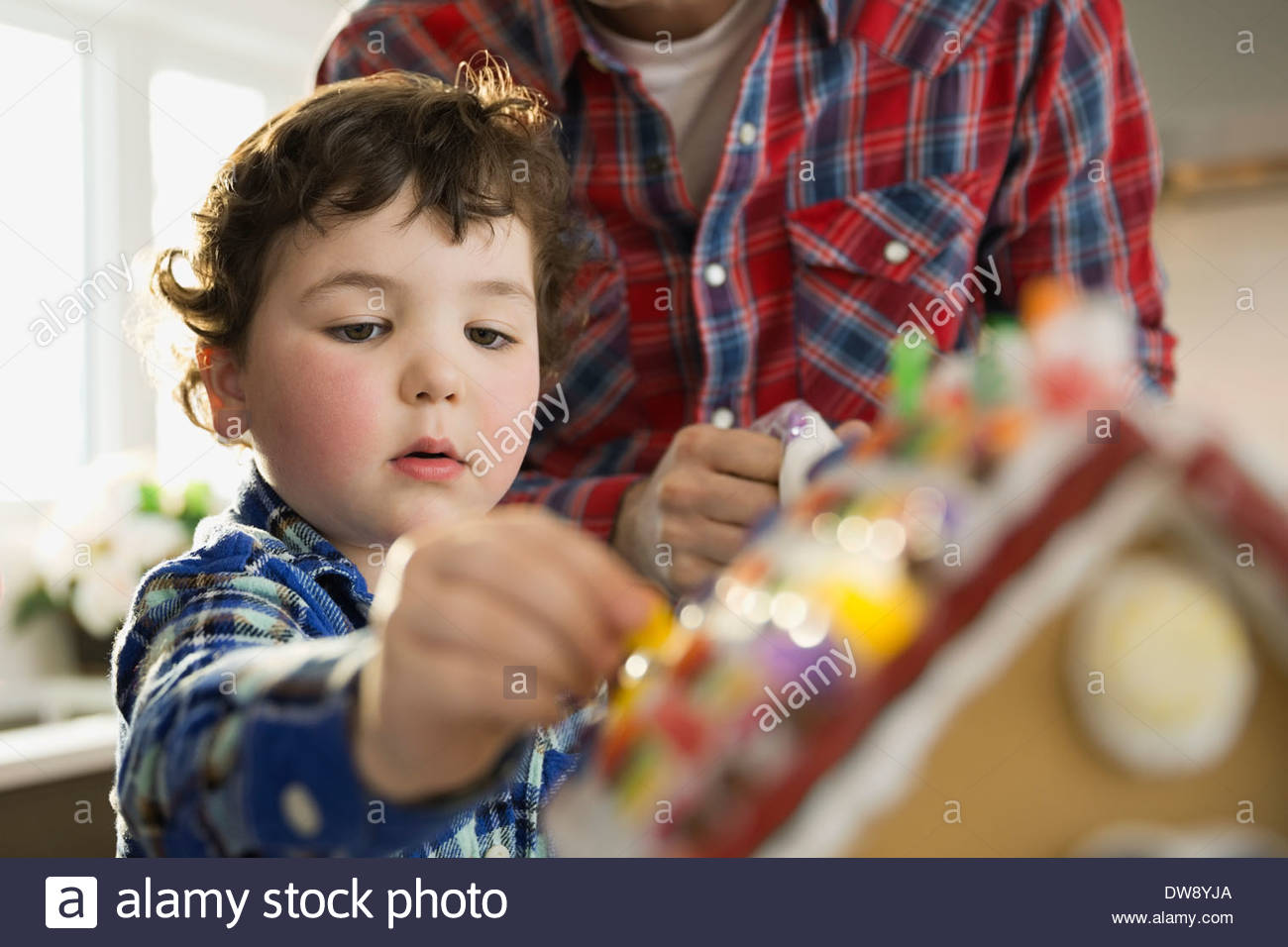 Cute boy decorating gingerbread house during Christmas - Stock Image