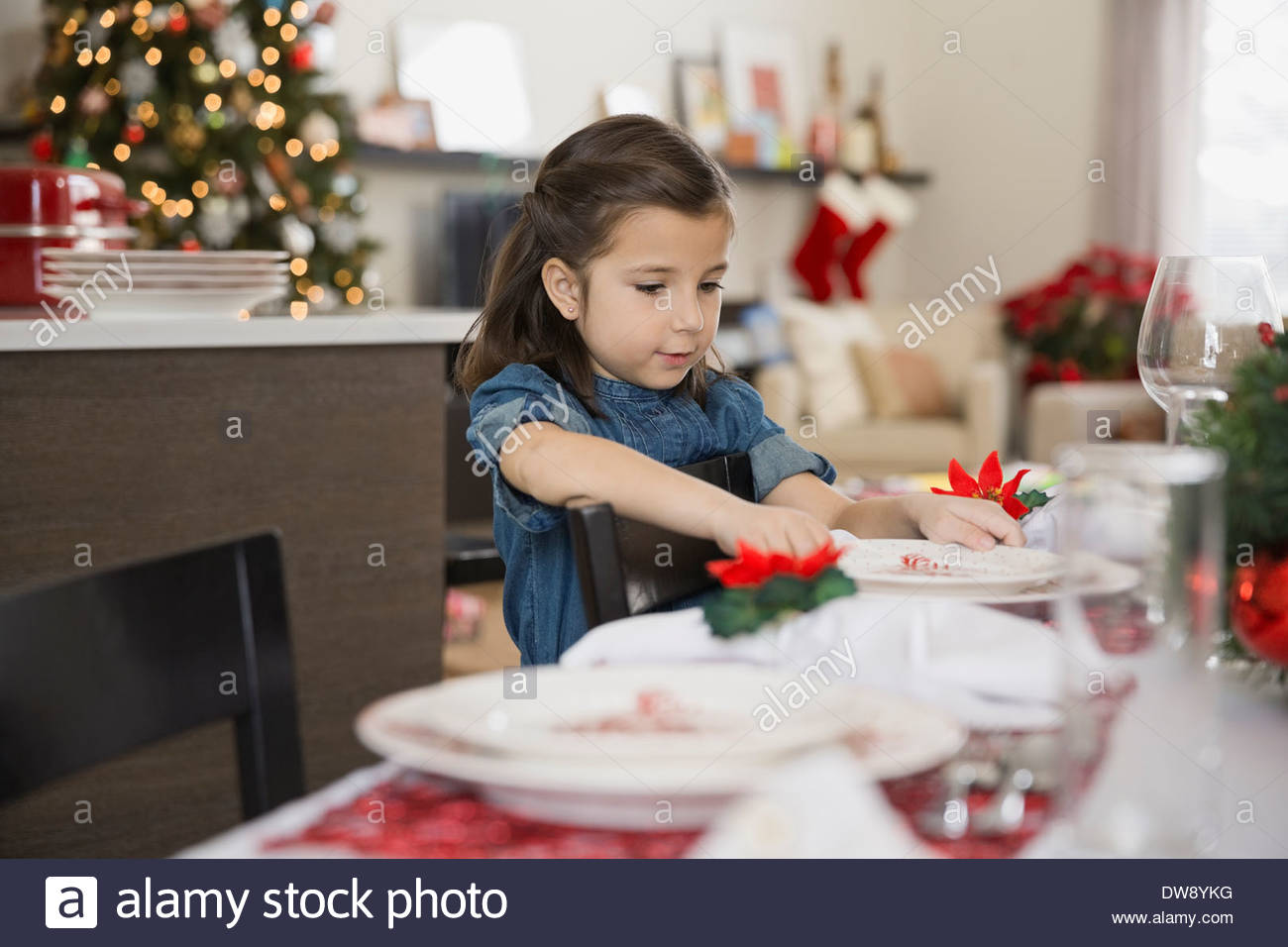Cute girl setting Christmas dining table - Stock Image