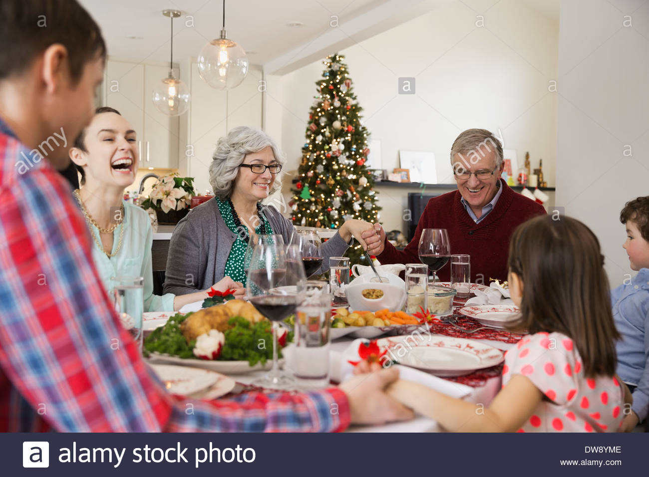Multi-generation family saying grace before Christmas dinner Stock Photo