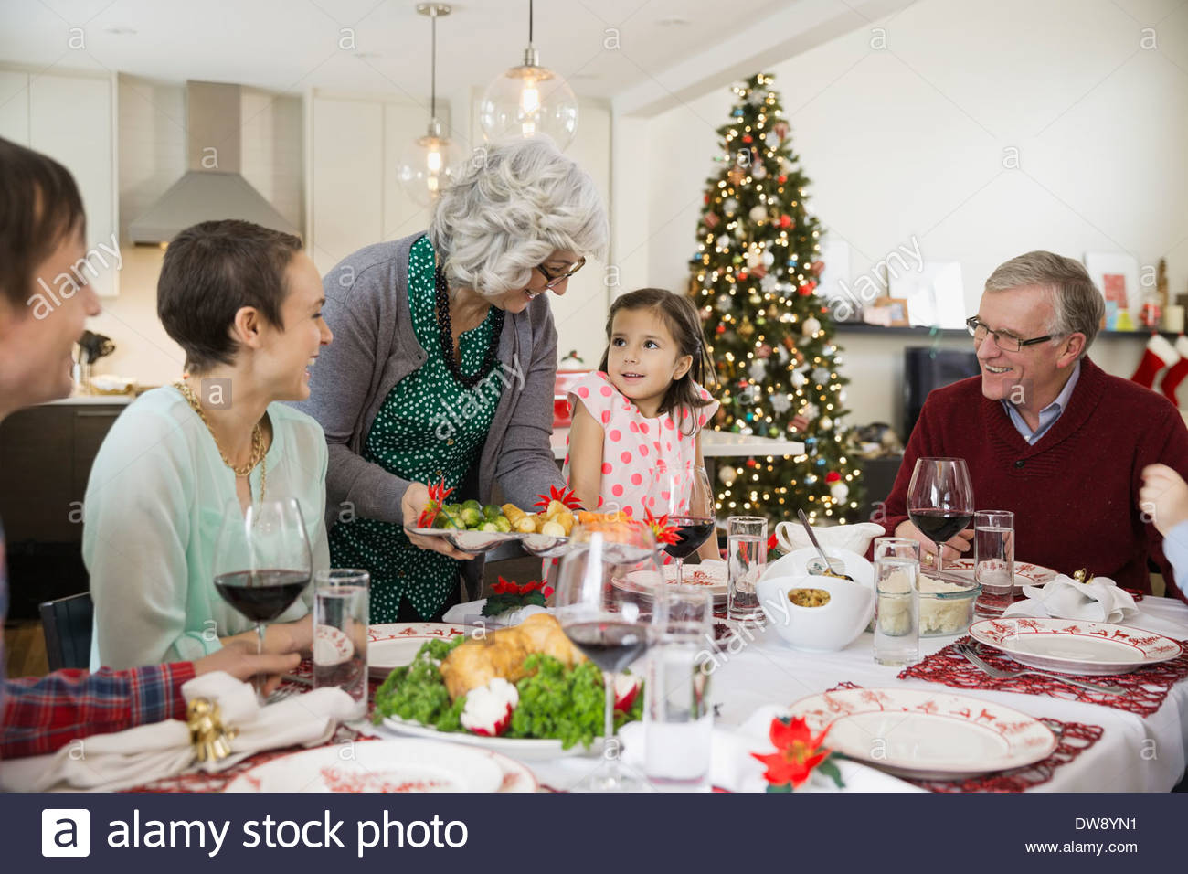 Grandmother serving food to family at Christmas dinner ...
