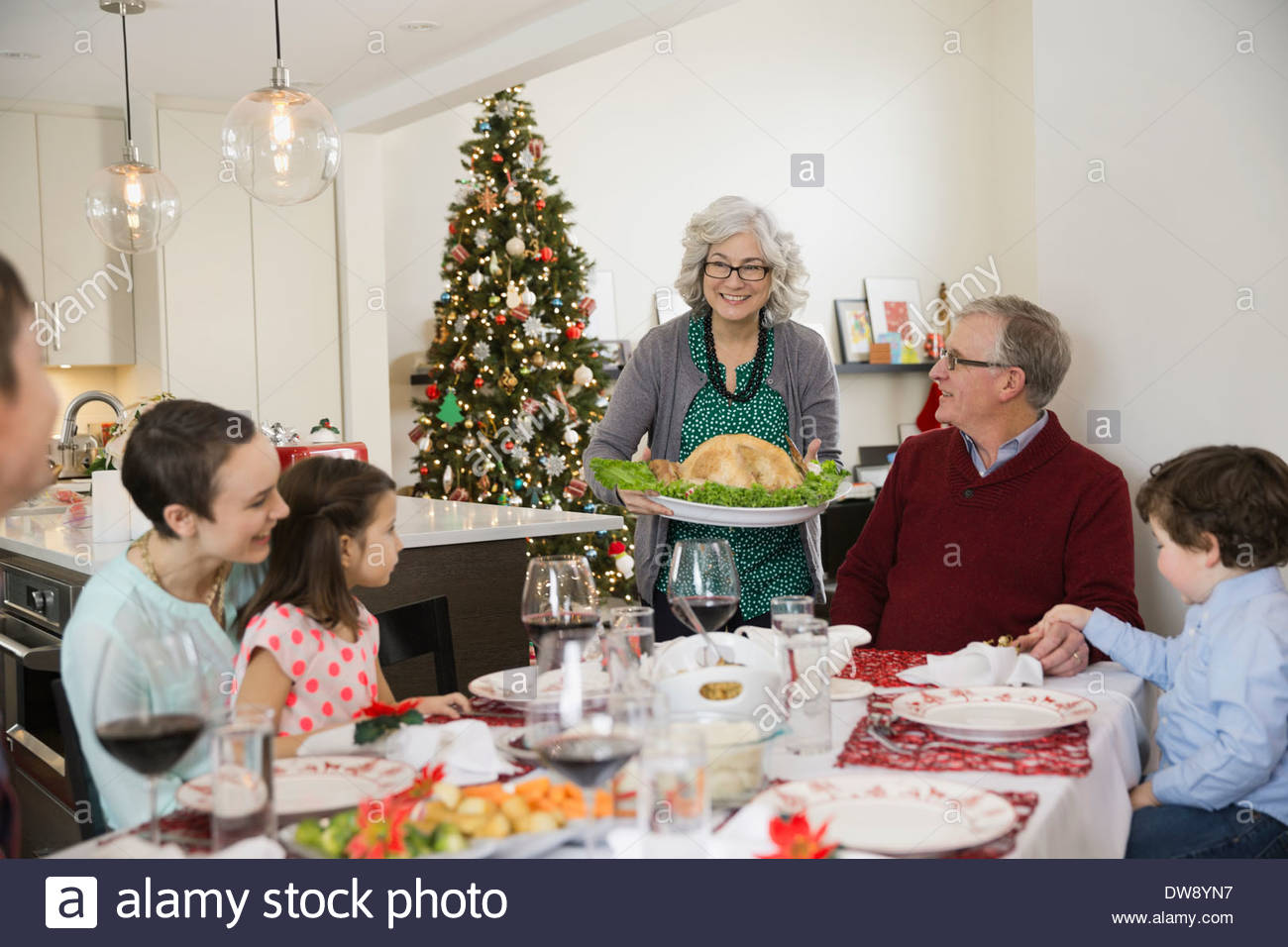Grandmother serving turkey to family at Christmas dinner - Stock Image
