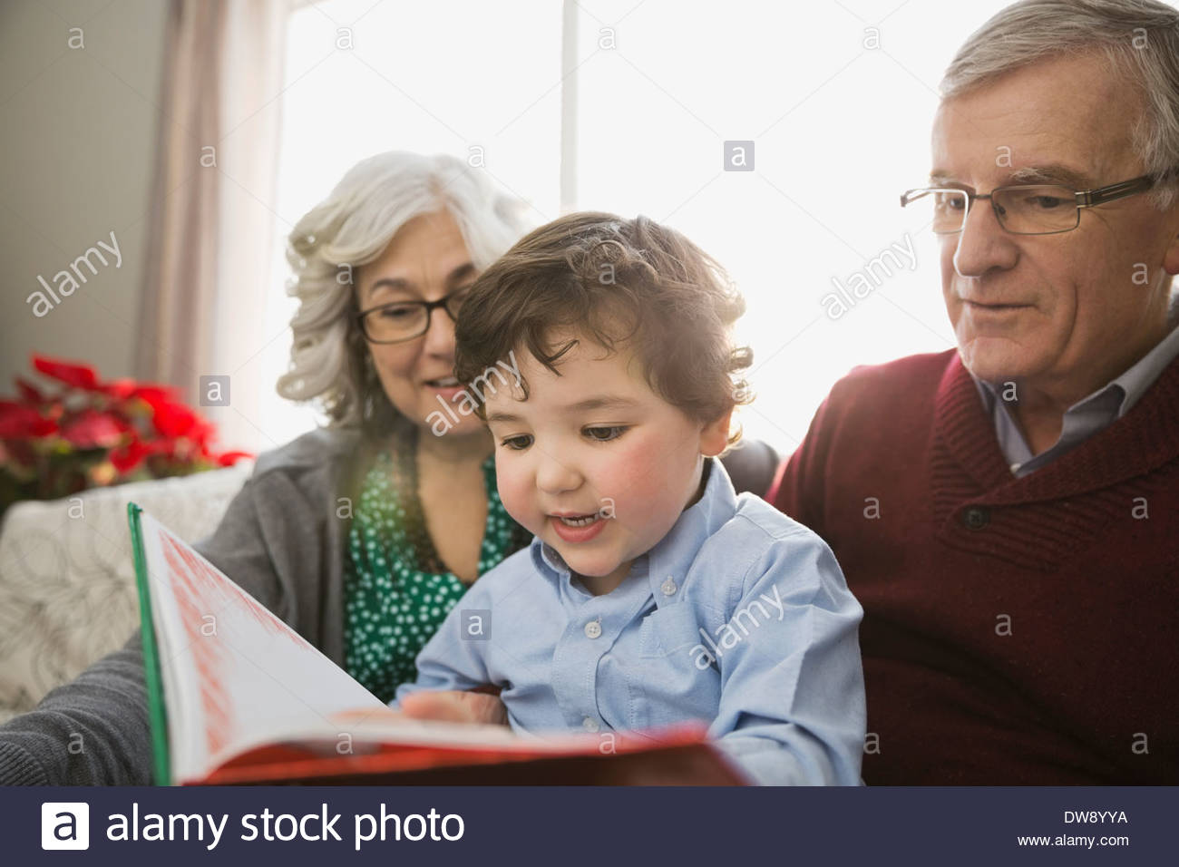 Grandparents and grandson reading book together - Stock Image