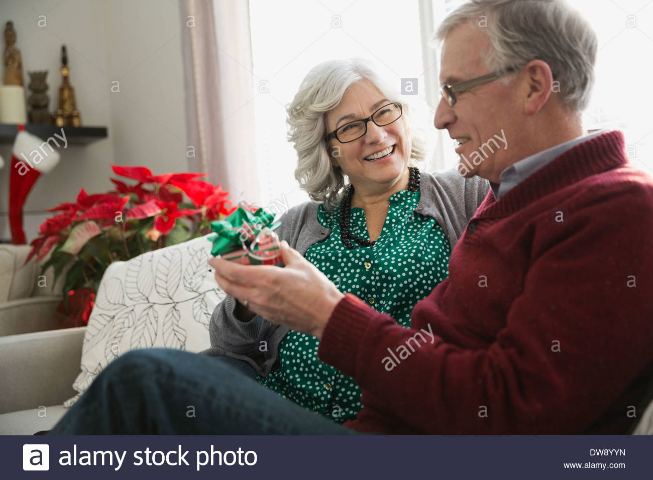 Senior couple sitting in living room exchanging Christmas gifts - Stock Image
