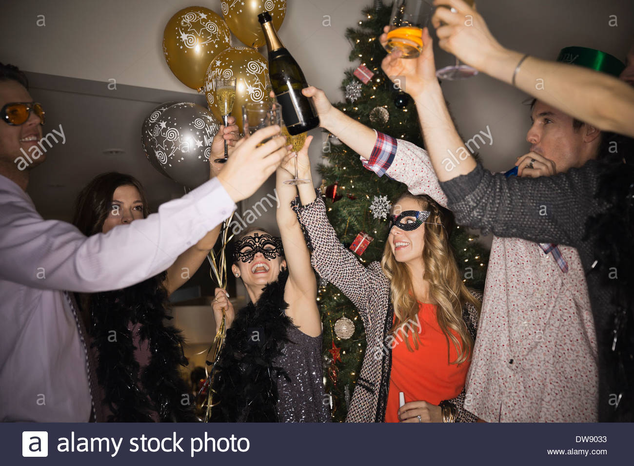 Friends celebrating New Years Eve party at home - Stock Image