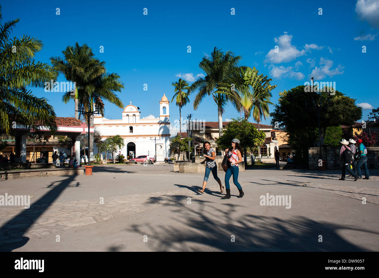 People stroll though Parque Central in the town of Copán Ruinas, Honduras. - Stock Image