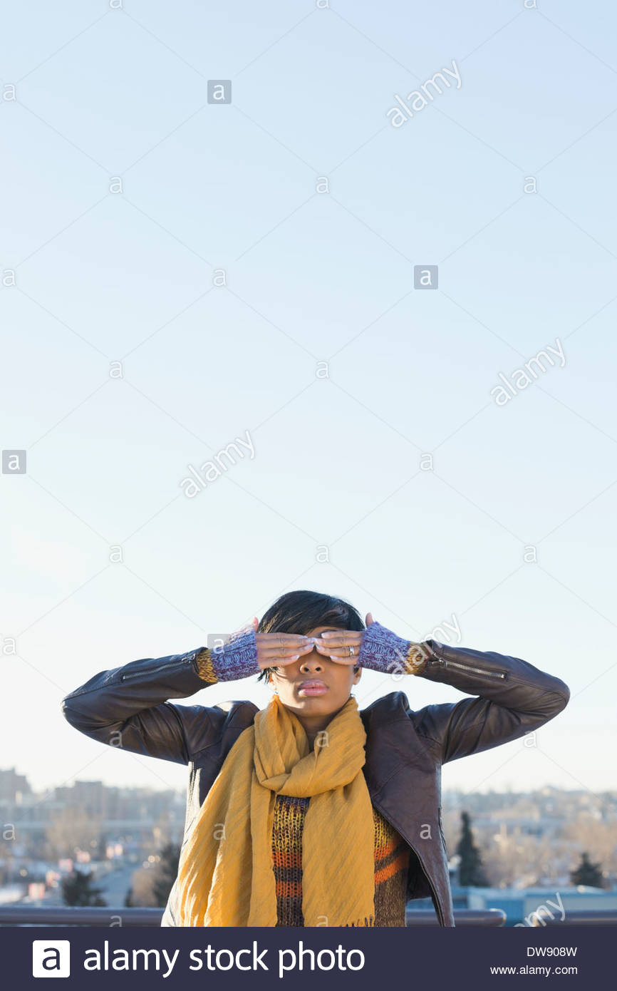 Woman covering eyes with two hands outdoors - Stock Image