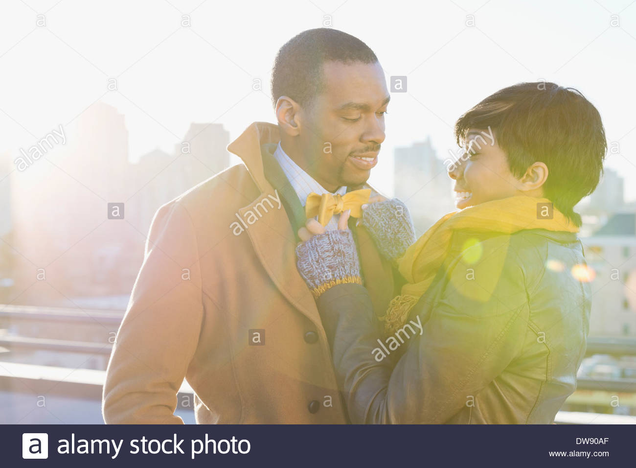 Smiling woman adjusting mans bow tie on patio - Stock Image