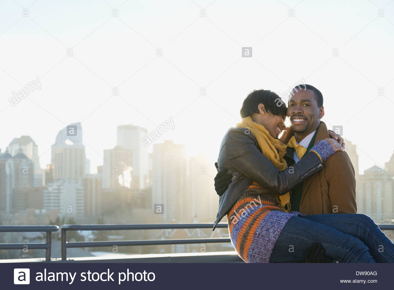 Portrait of man picking woman up outdoors - Stock Image