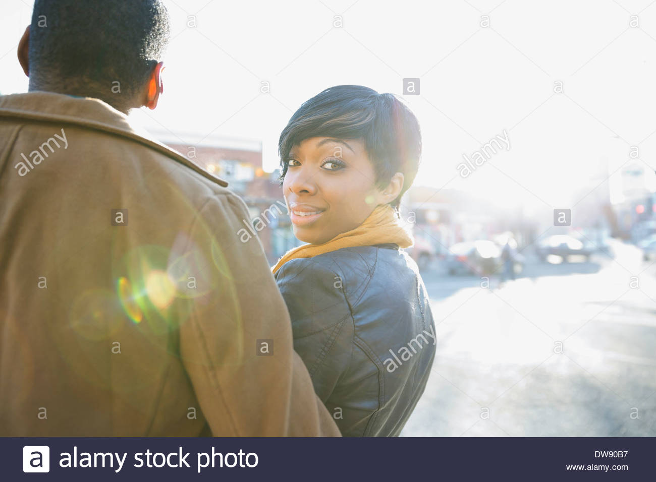 Rear view portrait of woman with man on city street - Stock Image
