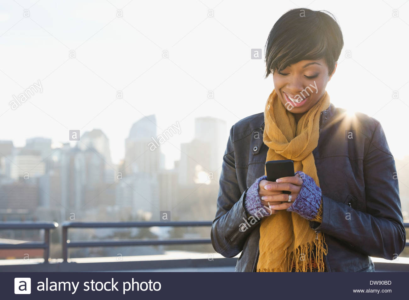 Smiling woman text messaging on patio - Stock Image