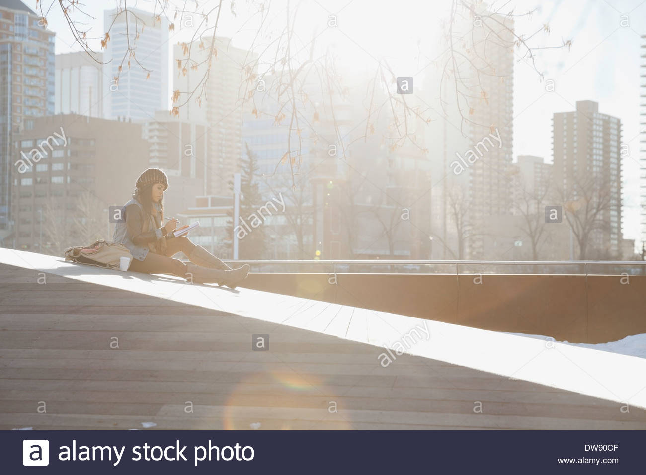 Woman sitting with coffee and journal against cityscape - Stock Image