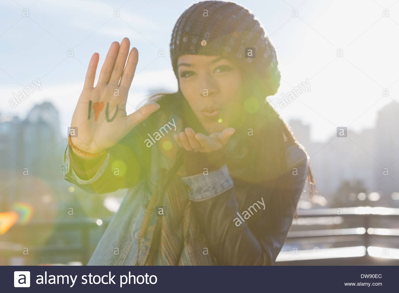 Woman showing I Love You sign and blowing kiss outdoors - Stock Image